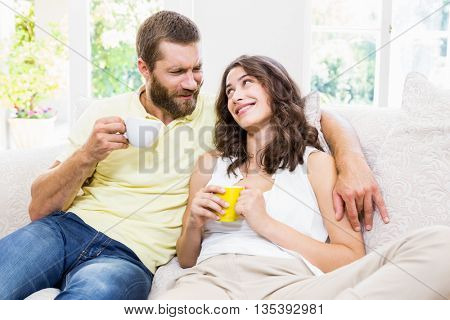 Couple interacting with each other while having coffee at home