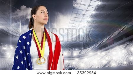 Athlete looking away with american flag and gold medals around his neck in a stadium