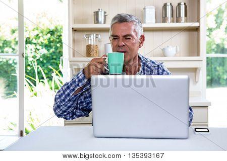 Senior man drinking coffee while using laptop in kitchen