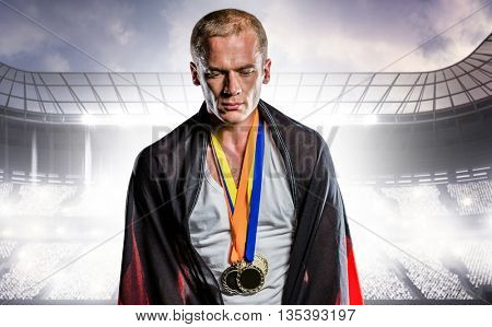 Athlete with german flag wrapped around his body against sports arena