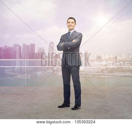 business, people and office concept - happy smiling businessman in dark grey suit over singapore city background