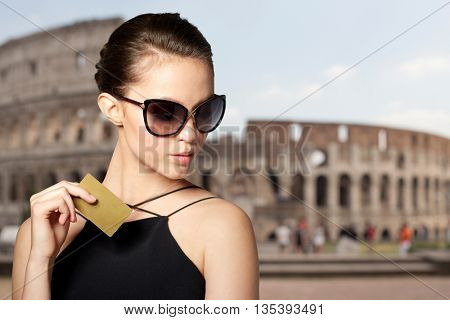 shopping tour, finances, travel, people and luxury concept - beautiful young woman in elegant black sunglasses with credit card over coliseum background