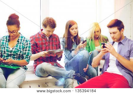 education and internet concept - students looking at their phones and tablet pc at school