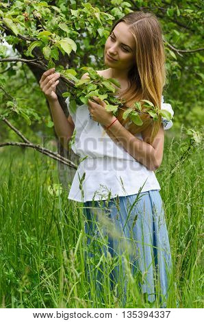 Young beautiful woman in long blue skirt and white blouse is standing in apple orchard