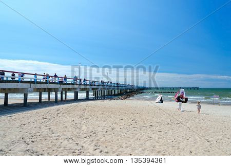 PALANGA LITHUANIA - JULY 12 2015: Unidentified people are relaxing on beach near the pier in popular resort town of Palanga Lithuania