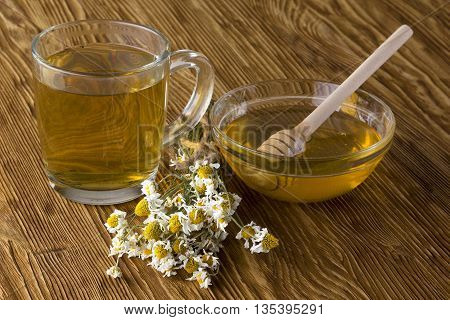 Cup of tea, honey and flowers on a old wooden background