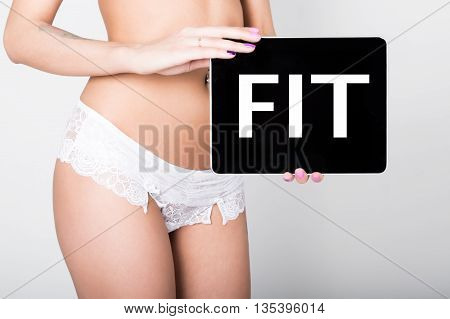 technology, internet and networking - close-up ass of girl in lacy lingerie, holding a tablet pc with fit sign. Adult content.