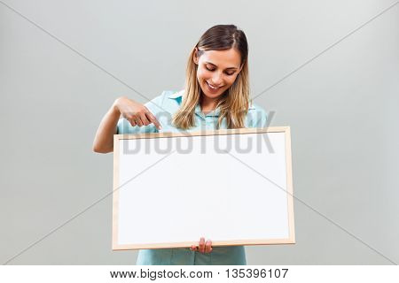 Beautiful nurse is holding and pointing at  whiteboard.