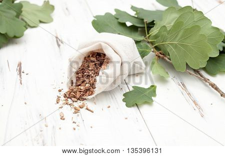 oak bark in a canvas bag with branches on white
