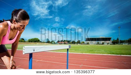 Athletic woman resting with hands on knees against facing view of run tracks