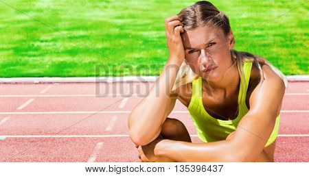 Sporty woman sitting down and feeling disappointed against race track