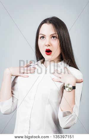 Young surprised woman on the gray background