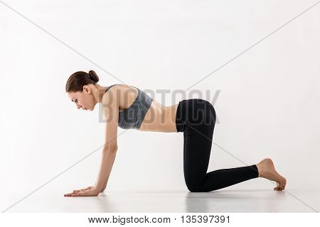 Young woman doing yoga exercise in white room