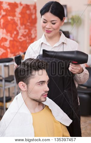 Cropped view of hairstylist drying man's hair. Side view of smiling hairdresser working in hairdressing salon with hair dryer.