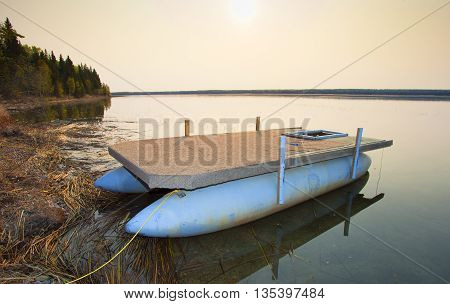 Pontoon boat tied up on shore shortly after the sun has risen