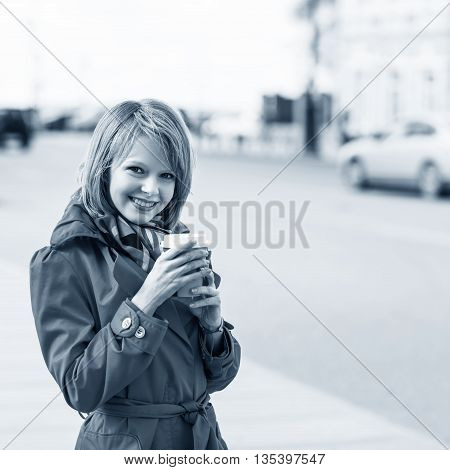 Young beautiful woman with to go coffee on the street