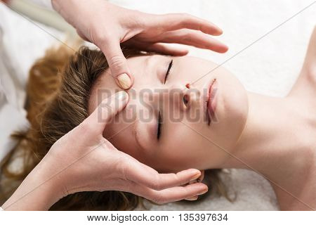 Young attractive woman getting face massage in the spa