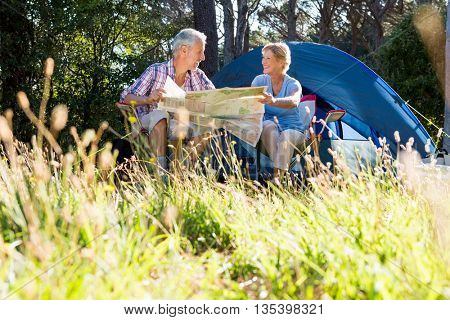 Mature couple smiling and reading a map on campsite