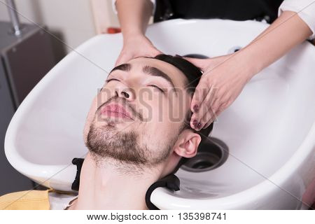 Closeup picture of young man lying with his eyes closed in beauty salon while having his hair washed in hairdressing salon.