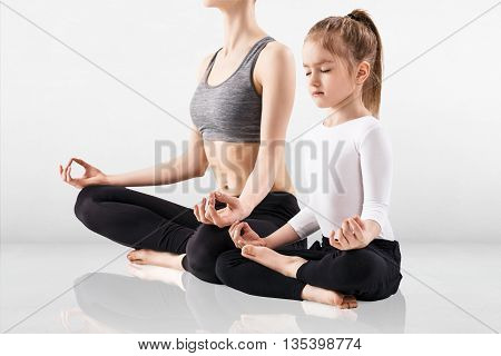 Young woman and her daughter doing yoga exercise in the gray room