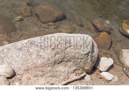 Big stone, pile of rock close river nature.