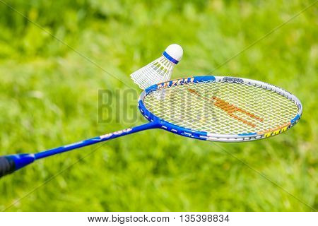 Shuttlecock and badminton racket and green background