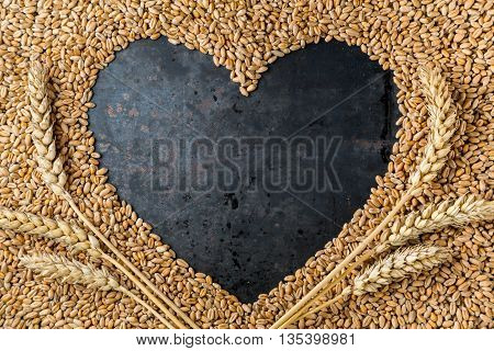Love harvest, Heart on ripe golden seeds of wheat on metal grey background, copy space, frame, top view