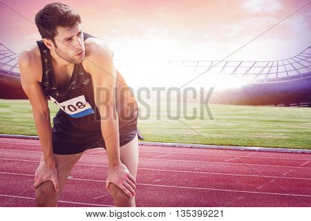 Athletic man resting with hands on knees against race track