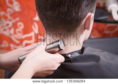 Closeup picture of handsome man having his hair cut with hair clipper in hairdressing salon. Hairdresser using hair clipper for hair.