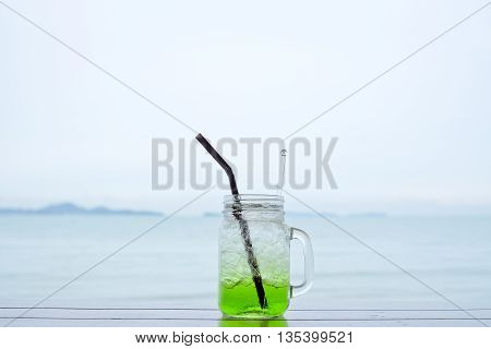 Kiwi soda in a glass , Kiwi fruit juice with view sea and sky