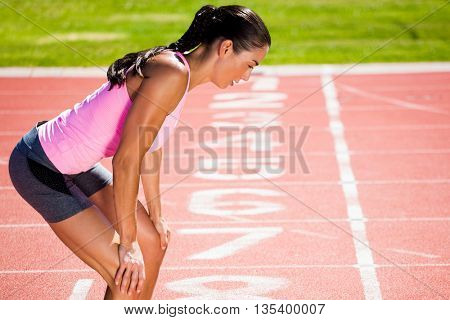 Profile view of breathless sportswoman against close up of the track starting point