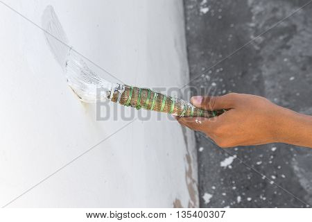 Painting walls.Painter paints using a brush,hand worker holding brush painting white on cement wall, and soft-focus background (select focus hand hold brush)