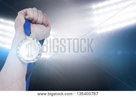 Close-up of hand holding olympic gold medal against spotlights