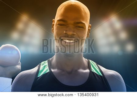 Portrait of happy sportsman is holding a shot put against composite image of spotlight
