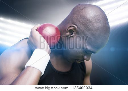 Portrait of sportsman practising shot put against spotlights