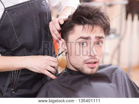 Closeup picture of handsome man having his hair cur by professional hairdresser in hairdressing salon. Young man looking at camera.
