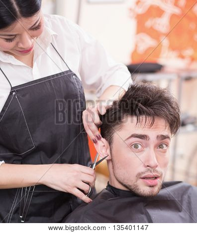 Picture of handsome man having his hair cur by professional hairdresser in hairdressing salon. Young man looking at camera.