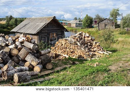Pile of birch firewood in front of old shed in northern russian village