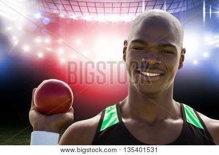 Portrait of happy sportsman is holding a shot put against american football arena