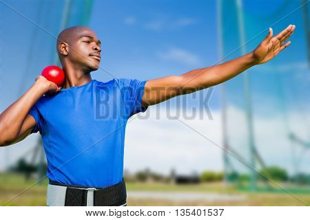 Front view of sportsman practising shot put against athletic field on a sunny day