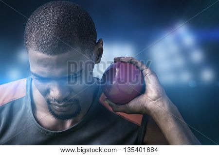 Portrait of sportsman practising shot put against composite image of spotlight