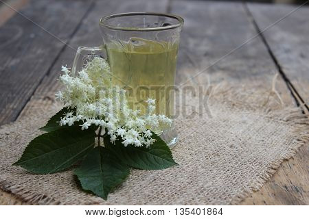 Glass cup with handle with tea and elderberry flowers