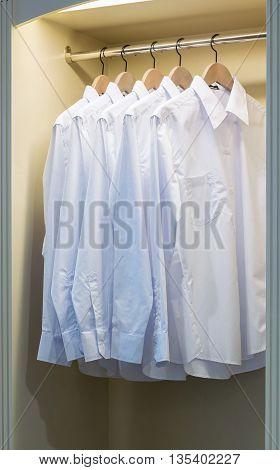 Row Of White Shirts Hanging On Coat Hanger In Wardrobe