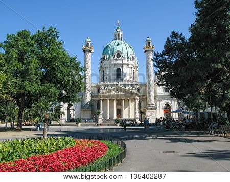 VIENNA, AUSTRIA - June 16, 2012: View of the St.Charles's Church (Karlskirche) with people in a sunny  summer day in Vienna.    Karlskirche built in baroque style and is located on the Karlsplatz in Vienna. Karlskirche  is  the   famous  tourist  attracti