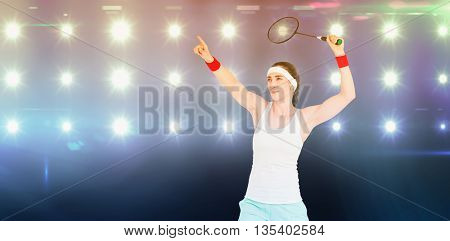 Female athlete playing badminton against composite image of blue spotlight