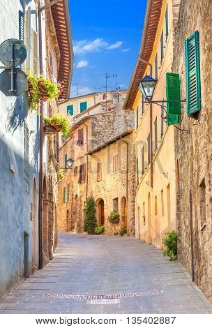 Montepulciano Italy. Old narrow street lined with stone blocks in the center of town with colorful facades. Tourists walking along the street.