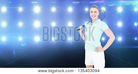 Pretty blonde playing badminton against composite image of blue spotlight