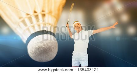 Badminton player playing badminton against composite image of spotlight