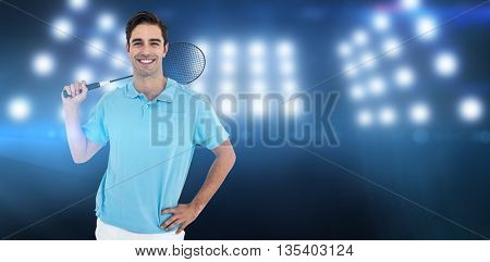 Portrait of badminton player standing with hand on hip against composite image of spotlight