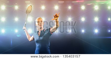 Badminton player playing badminton against composite image of blue spotlight